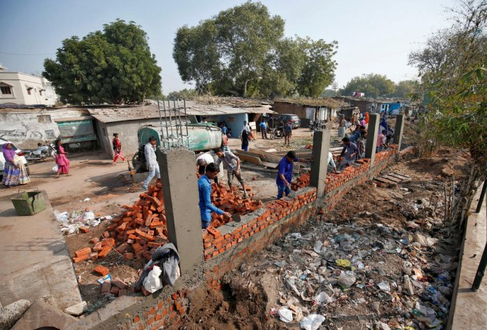 Construction workers build a wall along a slum area as part of a beautification drive along a route that US President Trump and India's PM Modi will be taking during Trump's visit later this month, in Ahmedabad
