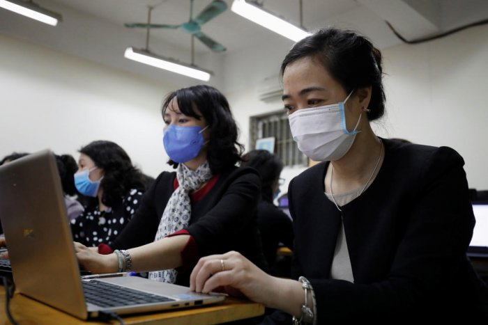 Teachers of Chu Van An school wear protective masks while attending an online study training course, while students are kept away from school during the coronavirus outbreak, in Hanoi, Vietnam February 15, 2020. (Reuters photo)