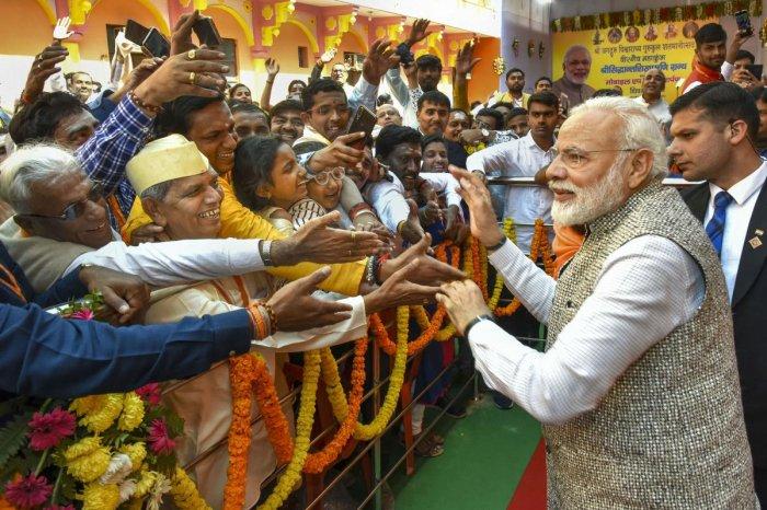 Prime Minister Narendra Modi meets people at the closing ceremony of the Centenary Celebrations of Shri Jagadguru Vishwaradhya Gurukul at Jangamwadi Math in Varanasi. (PTI Photo)