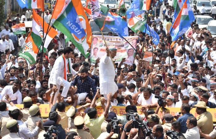 Congress leaders Dinesh Gundurao and Rizwan Arshad walk on barricades put up for crowd control during a protest against BJP, in Bengaluru on Saturday. DH Photo/Janardhan B K