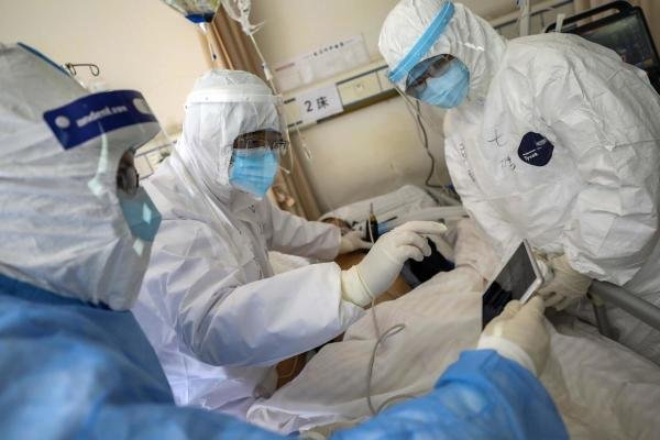 In this Sunday, Feb. 16, 2020, photo, medical personnel scan a new coronavirus patient at a hospital in Wuhan in central China's Hubei province. (AFP Photo)