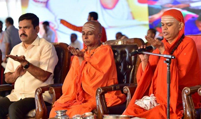 Chief Minister B S Yediyurappa's son B Y Vijayendra, Dr Basavalinga Pattadevaru of Hiremutt in Bhalki and Shivamurthy Murugha Sharana of Chitradurga perform 'Isthalinga pooja' at a convention of Sharnas in Bengaluru on Sunday. DH Photo/Ranju P