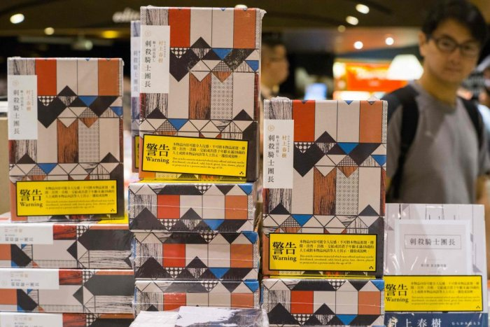 Copies of Japanese writer Haruki Murakami's latest novel 'Killing Commendatore' are displayed sealed in wrappers with yellow warning notices in a bookstore in Hong Kong. (AFP)