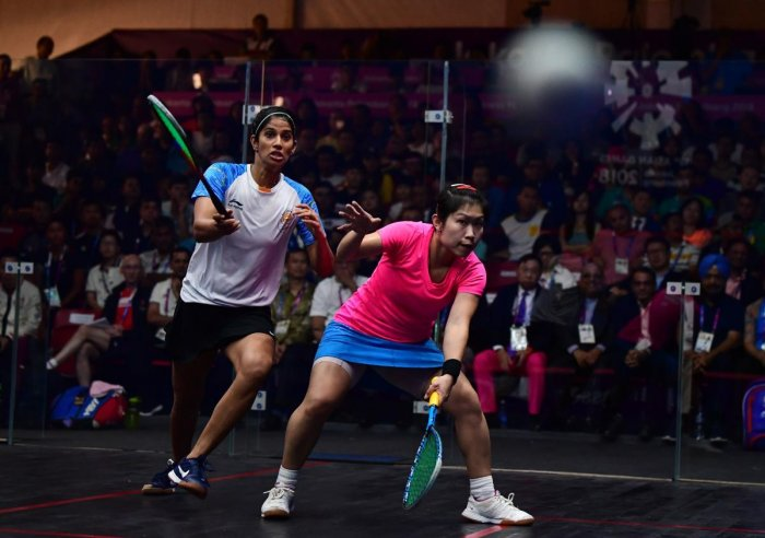 Hong Kong's Annie Au Wing-chi (right) hits a return against India's Joshna Chinappa in their women's team squash final match. AFP