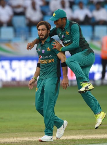 Easily done: Pakistan's Usman Khan is congratulated by a team-mate after dismissing Hong Kong batsman Scott McKechnie during their Asia Cup match on Sunday. AFP