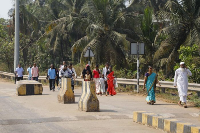 Passengers walk to board a bus in front of the toll gate in Talapady.