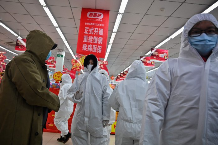 Pharmacy workers wearing protective clothes and masks serve customers in Wuhan. (AFP Photo)