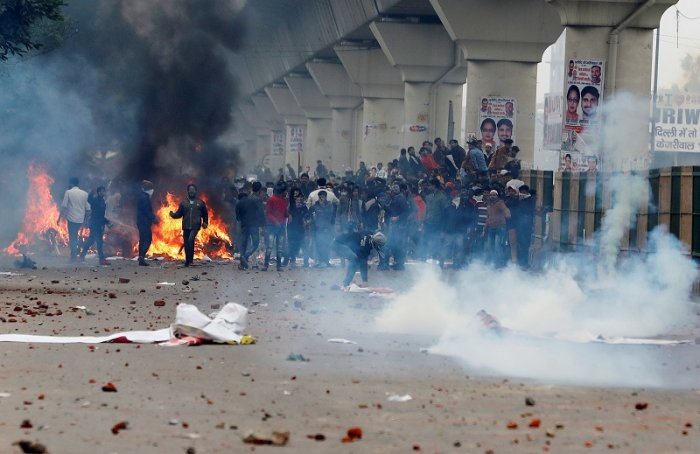 Demonstrators throw stones towards police during a protest against a new citizenship law in Seelampur, area of Delhi. (Reuters Photo)