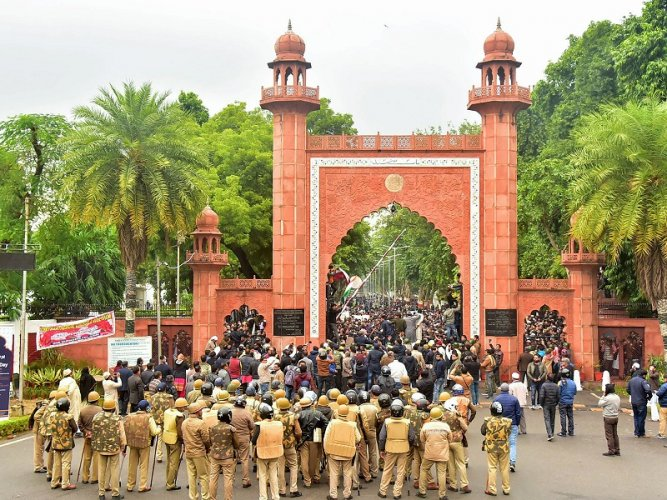 Police personnel stand guard outside Aligarh Muslim University (AMU) as students protest against the passing of Citizenship Amendment Bill, in Aligarh. (PTI Photo)