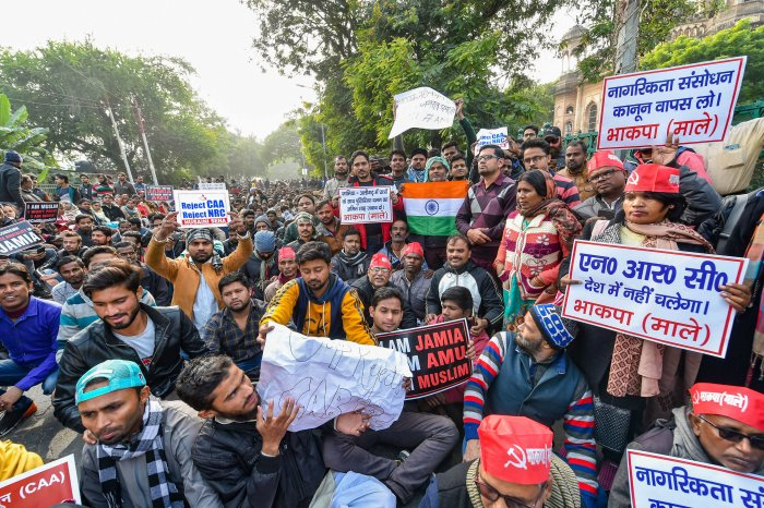 Protestors hold placards during an anti-Citizenship Act protest, at Parivartan Chowk in Lucknow. (PTI Photo)