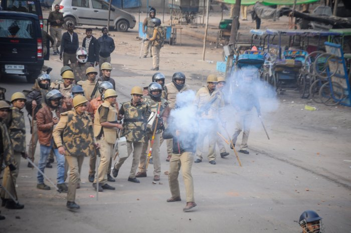 Police personnel fire tear gas shells during a protest against the Citizenship (Amendment) Act, at Babu Purwa in Kanpur. (PTI Photo)