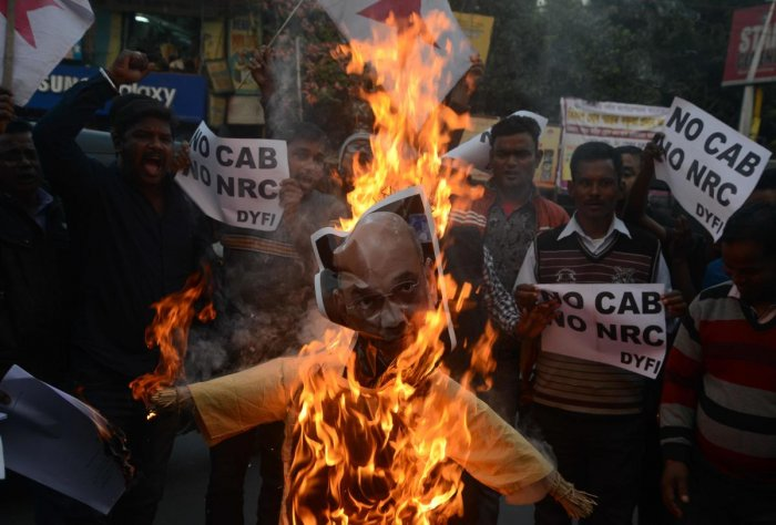 Indian left wing activists of Democratic Youth Federation of India (DYFI) shout slogans as they burn an effigy of India's Home Minister Amit Shah during a demonstration against the Indian government's Citizenship Amendment Bill in Siliguri. (AFP Photo)