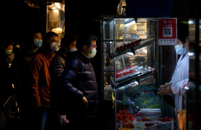 People wearing protective facemasks queue to order food from a stall in Shanghai on February 14, 2020. - Youan Hospital is one of twenty hospitals in Beijing treating coronavirus patients. AFP