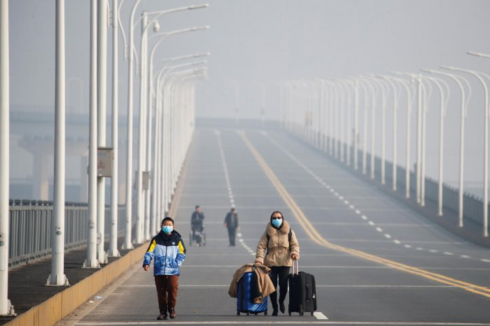 A mother and her son arrive from Hubei province at a checkpoint at the Jiujiang Yangtze River Bridge in Jiujiang