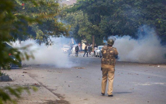 Policeman fires teargas shells at protestors of Citizenship Amendment Act at Mathura Road. PTI