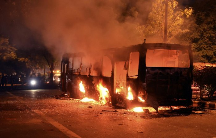 A DTC bus set on fire following protests against the passage of Citizenship Amendment Act near Mathura Road, in New Delhi. (PTI Photo)