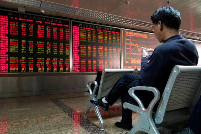 An investor uses his mobile phone in front of a stock quotation board at a brokerage office in Beijing, China January 3, 2020. (Reuters Photo)