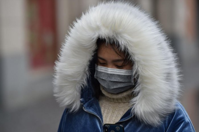 A woman wearing a protective facemask to help stop the spread of a deadly virus which began in the city, walks on a street in Wuhan in China's central Hubei province on January 25, 2020. (AFP Photo)