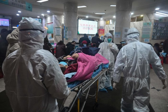 In this photo taken on January 25, 2020, medical staff wearing protective clothing to protect against a previously unknown coronavirus arrive with a patient at the Wuhan Red Cross Hospital in Wuhan. (AFP Photo)