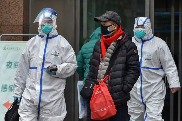 Medical staff wearing clothing to protect against a previously unknown virus walk outside a hospital in Wuhan on January 26, 2020. (AFP Photo)