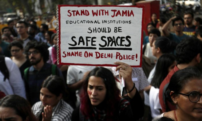 A woman holds a placard during a protest in solidarity with Jamia Millia Islamia university students after police entered the campus on Sunday in New Delhi, following a protest against a new citizenship law, in Mumbai. Reuters