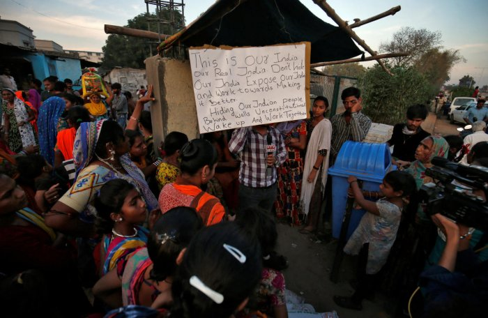 A placard hangs as residents gather to support Aswathy Jwala (not pictured), a social activist, who is on a hunger strike to oppose the building of a wall along a slum area, that authorities said was as built as part of a beautification drive along a route, that U.S. President Donald Trump and India's Prime Minister Narendra Modi will be taking during Trump's upcoming visit, in Ahmedabad, India, February 18, 2020. (Reuters Photo)