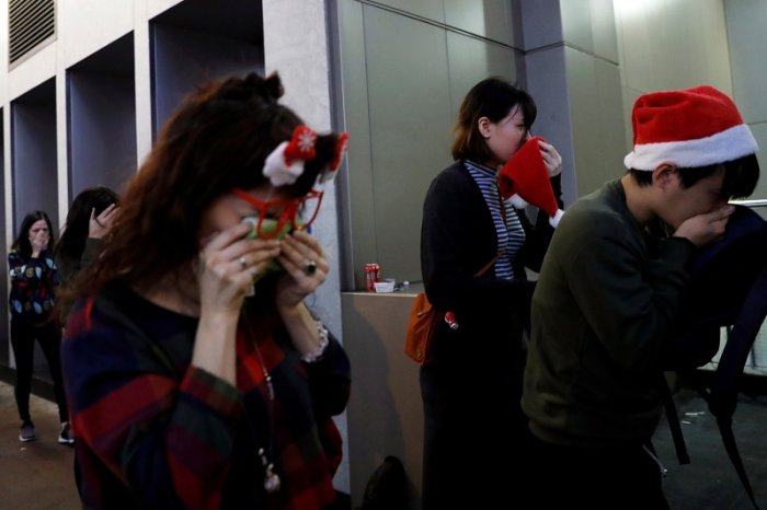 People wearing Santa hats react from tear gas during an anti-government protest on Christmas Eve in Hong Kong. (Reuters Photo)