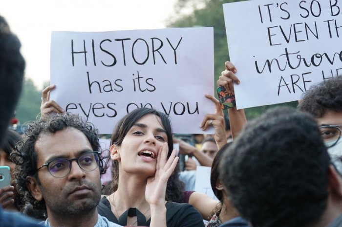 A young women shouts a slogan during a protest against CAA in front of Town hall on Sunday. (DH Photo)