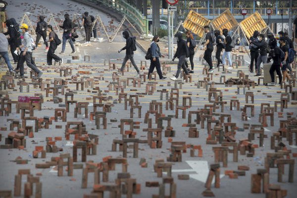 Protesters walk past barricades of bricks on a road near the Hong Kong Polytechnic University in Hong Kong. (AP photo)