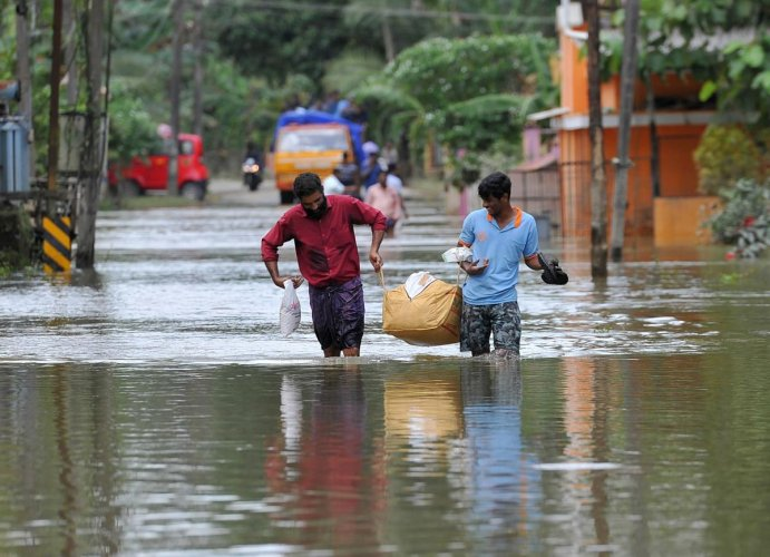 In this file photo taken on August 21, 2018 men carry food and water aid distributed to people stranded by floods in Pandanad in Alappuzha District in the south Indian state of Kerala. AFP
