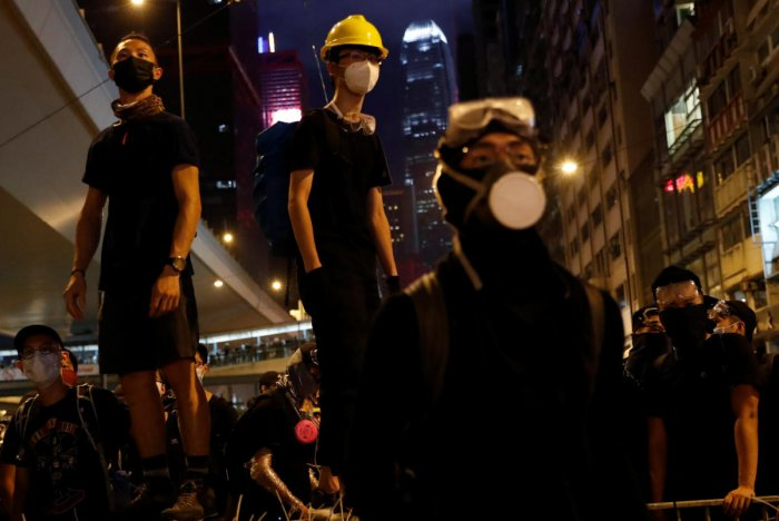 Anti-extradition bill demonstrators stay on barriers as they face riot police, after a march to call for democratic reforms, in Hong Kong, China July 21, 2019. (Photo by Reuters)