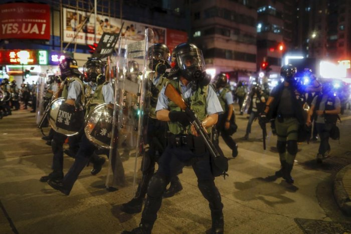 Hong Kong:Police in riot gear march on a street as they confront protesters in Hong Kong on Wednesday, Aug. 14, 2019. German Chancellor Angela Merkel is calling for a peaceful solution to the unrest in Hong Kong amid fears China could use force to quell p