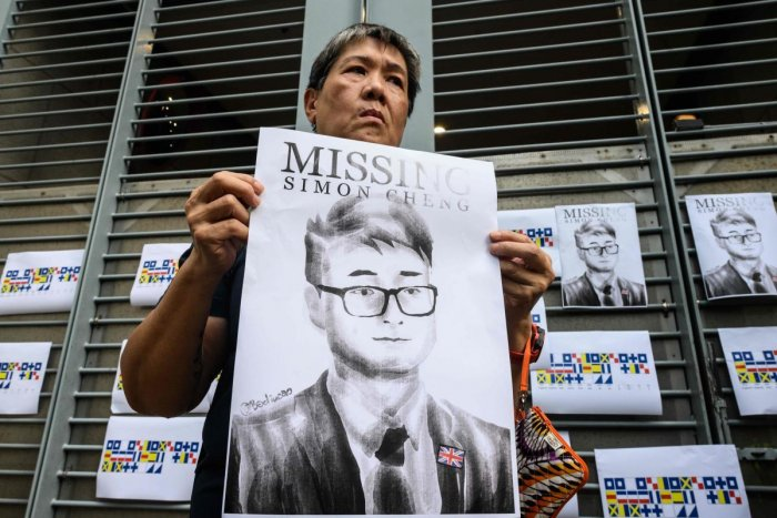 An activist holds an illustration of Simon Cheng during a gathering outside the British Consulate-General building in Hong Kong. (AFP Photo)