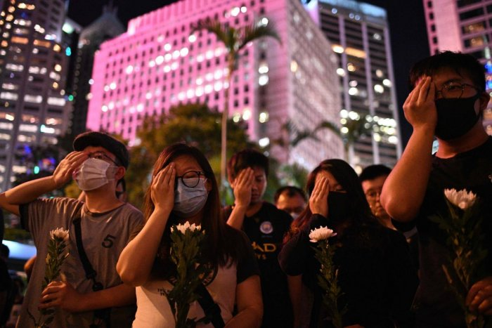 Protesters cover their right eyes as they attend the Stand in Silence for the 74th Anniversary of the Liberation of Hong Kong gathering at the Cenotaph in Hong Kong (AFP Photo)