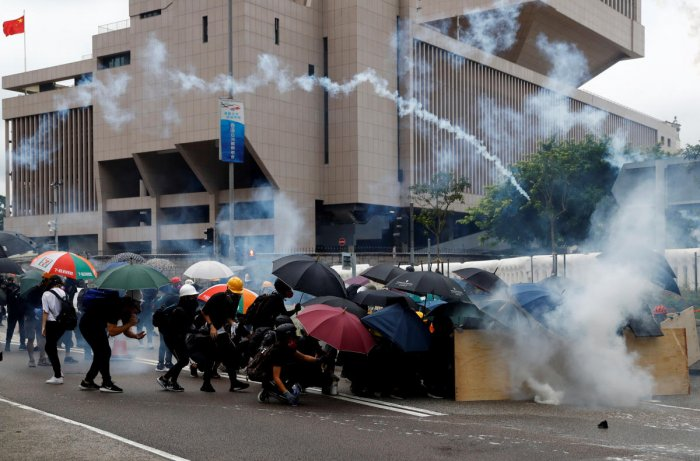 Demonstrators take cover as police fires tear gas during a protest in Hong Kong. Reuters photo