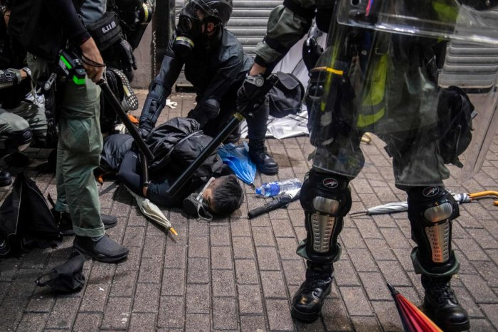TOPSHOT - A protester (C) is detained by police during clashes with protesters at the Wan Chai district in Hong Kong on October 6, 2019. - Hong Kong was rocked by fresh violence on October 6 as tens of thousands hit the streets to defy a ban on face masks