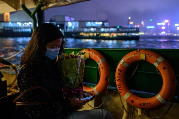 A woman wears a face mask as a preventative measure against the COVID-19 coronavirus as she travels on a ferry from Kowloon to island side of Hong Kong on February 14, 2020. AFP