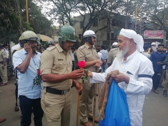 Izaz Ahmed, an business man, offers roses to policemen deputed on duty at Ambedkar circle in Hubballi during anti-CAA protest