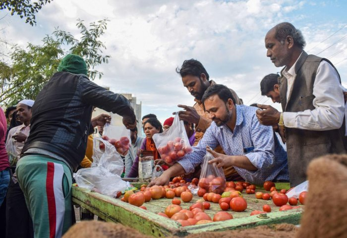 Residents buy vegetables at a shop after curfew was relaxed in Jabalpur. PTI