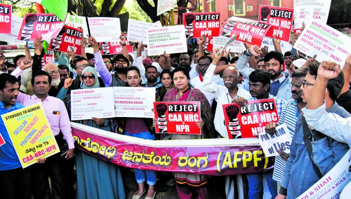 Protesters display placards and raise slogans during a protest against the Citizenship Amendment Act, National Register of Citizenship and National Population Register near Mysore Bank Circle on Monday. DH photo/Janardhan B K