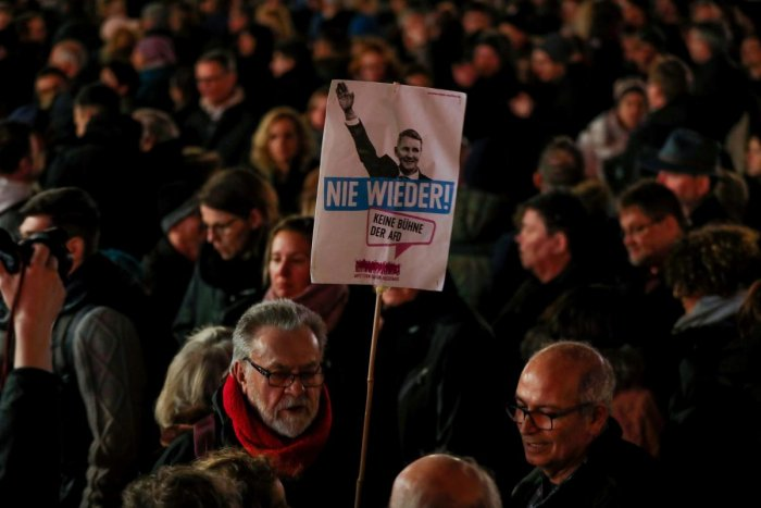 "A man holds a placard featuring Regional leader of AfD Thuringia Bjoern Hoecke and the words ""Never again"" during a vigil in Hanau, near Frankfurt am Main, western Germany"
