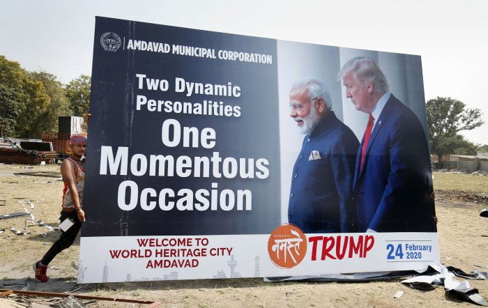 Workers carry a hoarding with pictures of the U.S. President Donald Trump and India's Prime Minister Narendra Modi as preparations are underway for Trump's forthcoming 'Namaste Trump' event, in Ahmedabad. (Credit: PTI Photo)