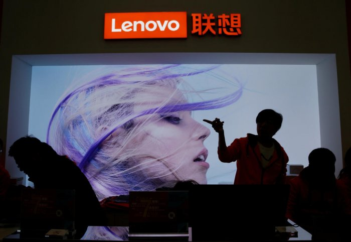 FILE PHOTO: An employee gestures next to a Lenovo logo at Lenovo Tech World in Beijing, China November 15, 2019. REUTERS/Jason Lee/File Photo