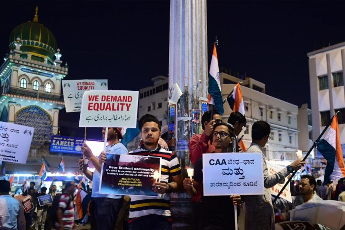Protesters hold candles and display placards during a protest against CAA, NRC, NRP and violence. (PTI Photo)
