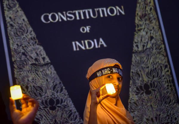 A Muslim girl holds LED-bulb light during a protest against CAA, NRC and NPR, in Bengaluru, Friday, Jan. 24, 2020. (PTI Photo)