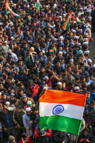 Anti-CAA protestors waves tri-colours as they celebrate the 71st Republic Day at Shaheen Bagh in New Delhi, Sunday, Jan. 26, 2020. Protests have been going on at Shaheen Bagh for over a month against the Citizenship Amendment Act (CAA) and proposed Nation