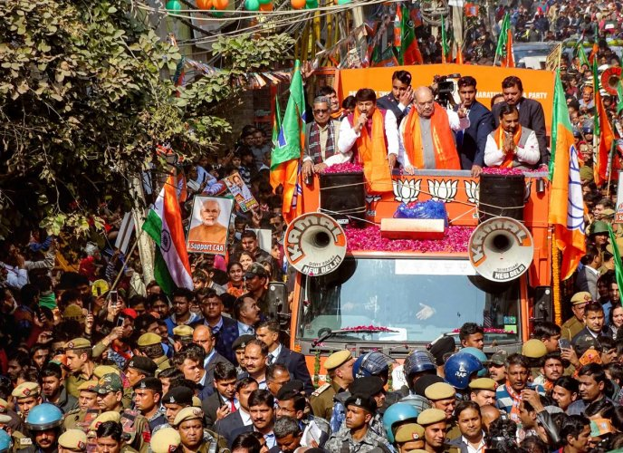Union Home Minister and senior BJP leader Amit Shah flashes victory sign during an election campaign roadshow for Delhi Assembly elections, at Ghonda in east Delhi, on Sunday. PTI
