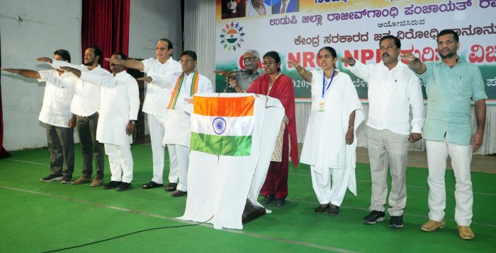 Speakers recite the Preamble to the Constitution and take oath at a programme at Town Hall in Ajjarkadu in Udupi on Thursday.