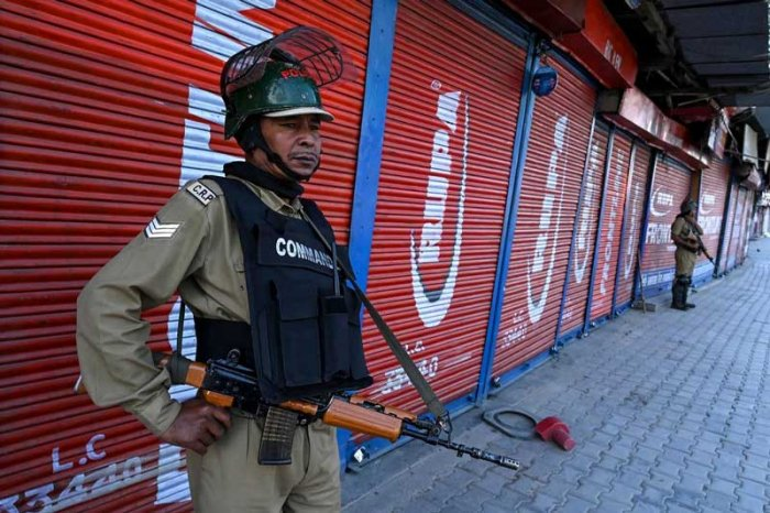 Security personnel stand guard in front of closed shops in Srinagar. (AFP Photo)