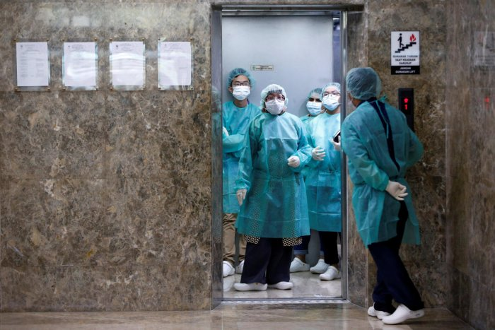 Journalists wear protective suits inside an elevator as they prepare for a media visit to Indonesian Health Ministry's Laboratorium for Research on Infectious-Diseases, following the outbreak of the new coronavirus in China, in Jakarta, Indonesia, Februar